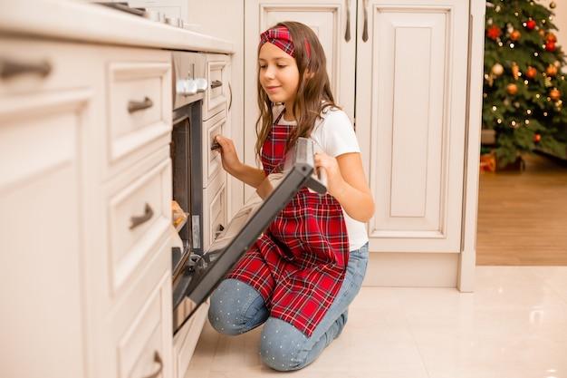 Маленькая девочка на кухне готовит рождественский ужин