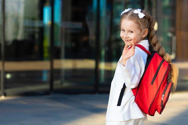 Маленькая девочка в военной форме идет в первый класс, машет рукой. счастливый смеющийся ребенок обратно в школу. ребенок с красным портфелем в кампусе.