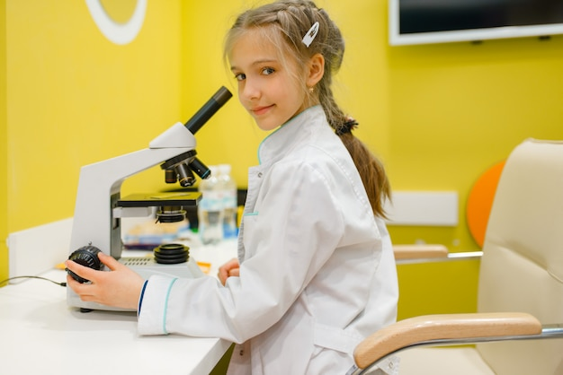 顕微鏡で座っていると医師を再生の制服を着た小さな女の子