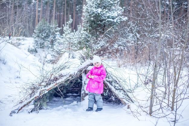 暖かい服を着た少女が冬の森の針葉樹の枝から小屋を建て、冬に屋外で遊ぶ
