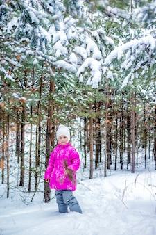 冬の森で遊んで、冬に屋外で時間を過ごす暖かい服を着た少女