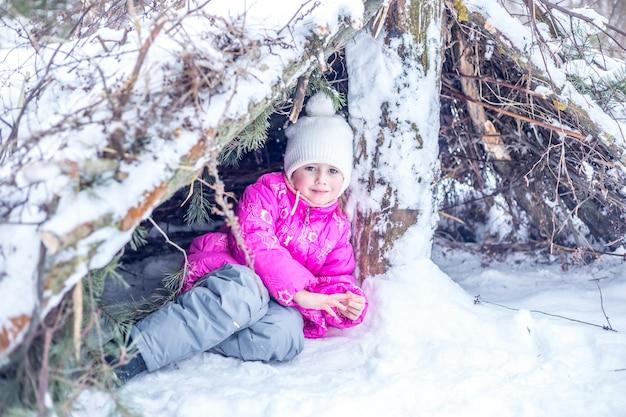 暖かい服を着た少女は、冬の森の針葉樹の枝から小屋で遊んで、冬に屋外で時間を過ごします