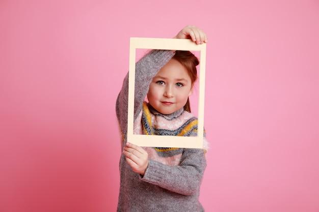 ローザバッハグラウンドのフレームを通して見ている暖かいドレスを着た少女。