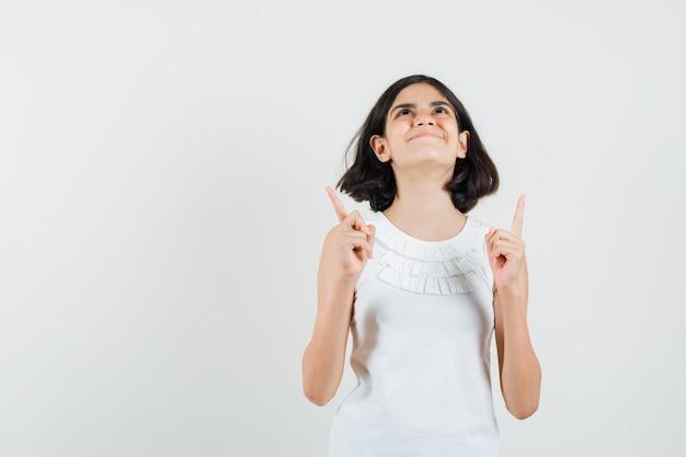 白いブラウスを着た少女が上を向いて感謝している正面図。