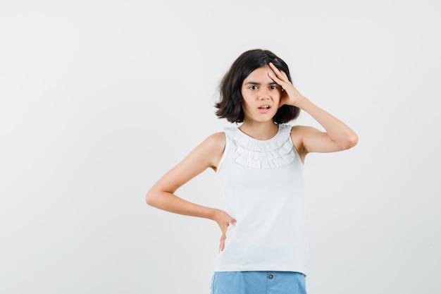 白いブラウス、ショートパンツで手をつないで物忘れをしている少女、正面図。