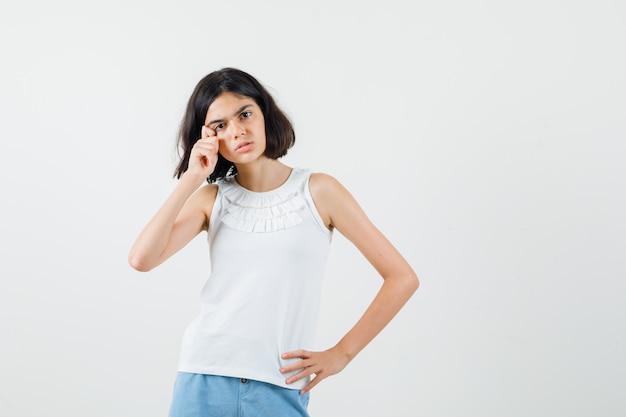 Маленькая девочка в белой блузке, шортах вытирая слезы пальцами и грустно, вид спереди.