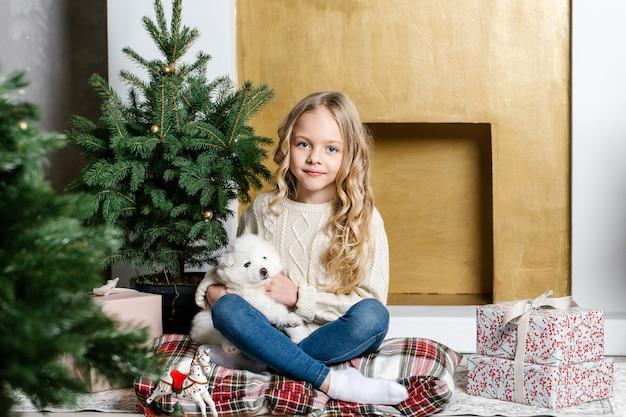 Маленькая девочка в белой одежде сидит на полу возле дерева с белым щенком самоеда и улыбается.
