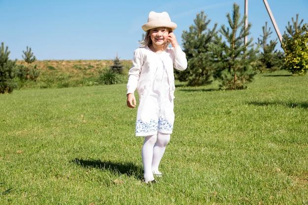 Маленькая девочка в белом платье и панама в солнечный летний день