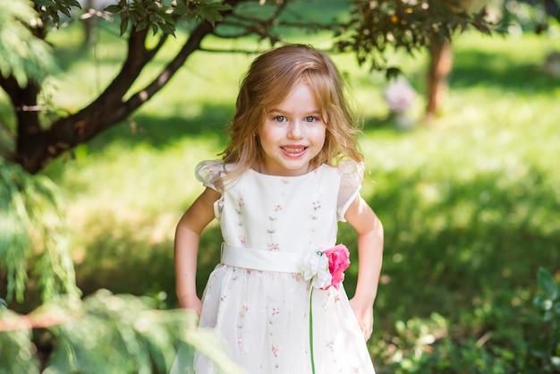 公園を歩いて笑顔の白いドレスを着た少女。子供のための美しい髪型とメイク。