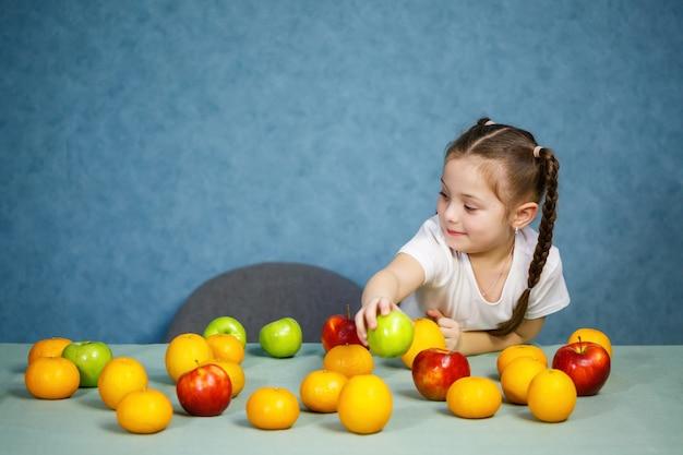 白いtシャツを着た少女が果物で遊んでポーズをとる