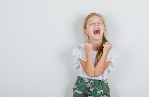 흰색 티셔츠에 어린 소녀, 축하하고 쾌활한 찾고 주먹에 손을 쥐고 치마