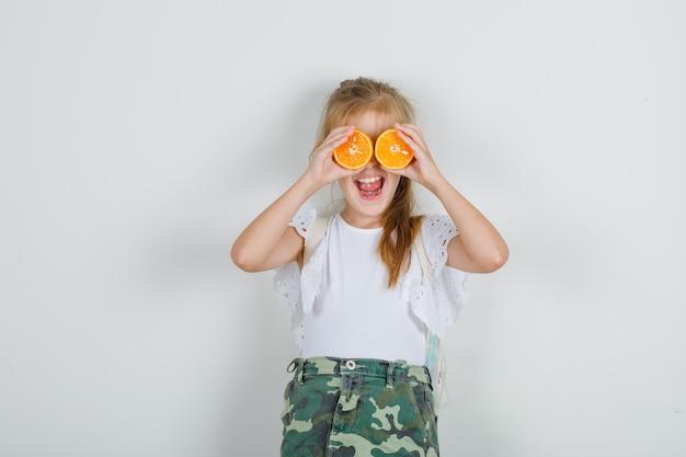 Маленькая девочка в белой футболке, юбка закрывает глаза апельсинами и выглядит жизнерадостной