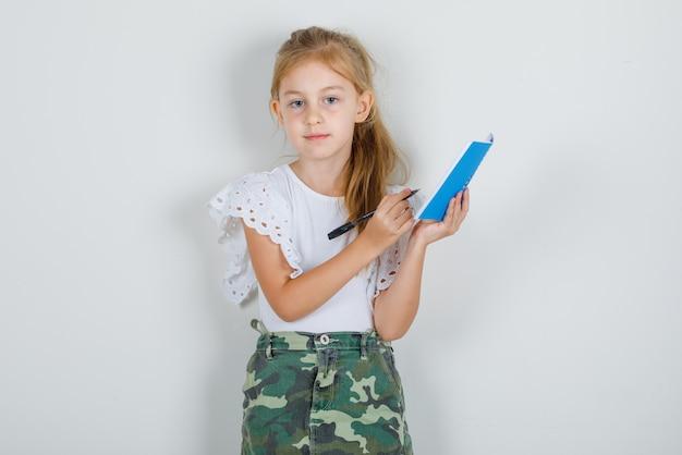 白いtシャツ、コピーブックとペンを保持しているスカートの少女