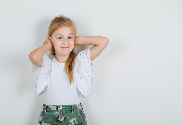 白いtシャツ、手で耳を押しながら陽気なスカートの少女