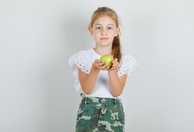 Маленькая девочка в белой футболке, юбка держит зеленое яблоко