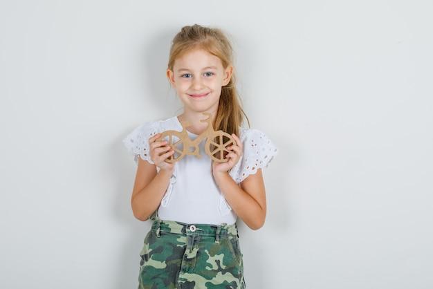 Маленькая девочка в белой футболке, юбке держит деревянную велосипедную игрушку и выглядит веселой