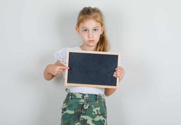 흰색 티셔츠에 어린 소녀, 칠판에 손가락을 가리키는 치마