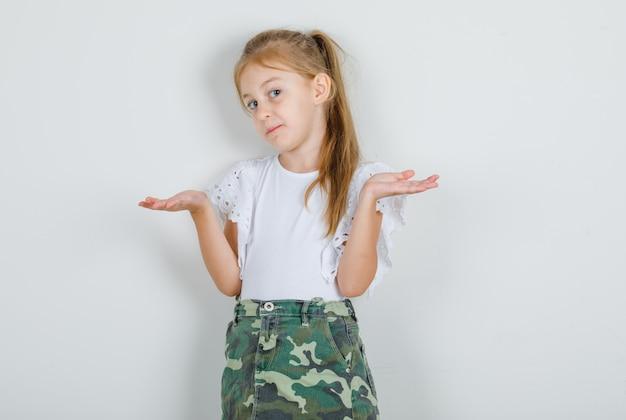 白いtシャツ、無力なジェスチャーを示し、混乱しているスカートの少女