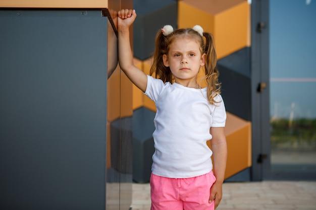 흰색 티셔츠를 입은 어린 소녀. 로고 또는 디자인을 위한 공간입니다. 인쇄용 목업