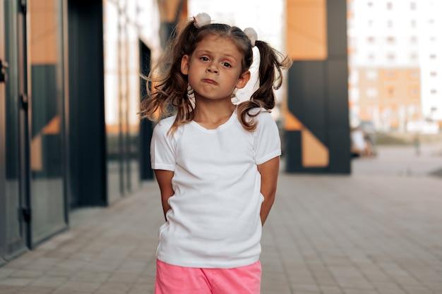 로고 또는 인쇄용 디자인 모형을 위한 흰색 티셔츠 공간에 있는 어린 소녀