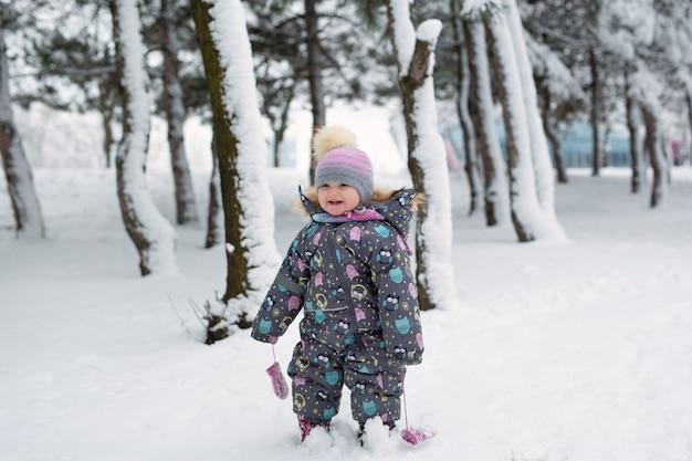 눈 덮인 숲에서 겨울에 어린 소녀.