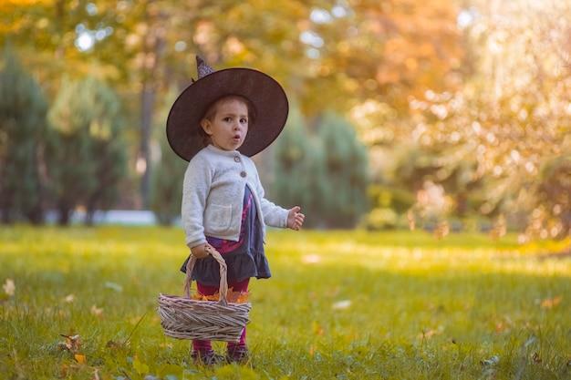 黄色の葉でいっぱいのバスケットと秋の公園でハロウィーンの魔女の衣装を着た少女。子供の頃、カーニバル。
