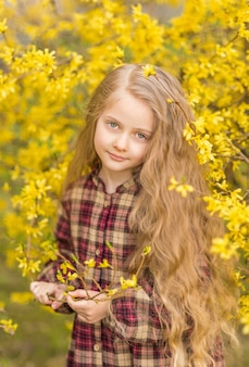 彼女の手に黄色い花を持つ少女。黄色い花を背景にした子供。子供の春の肖像画