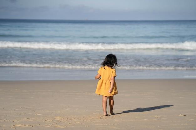 바다 해안에서 재생하는 노란색 드레스에 어린 소녀.