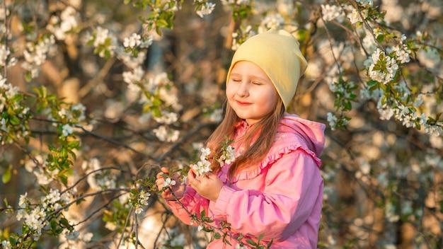 黄色の帽子の少女は花の背景の木に立ち向かいます