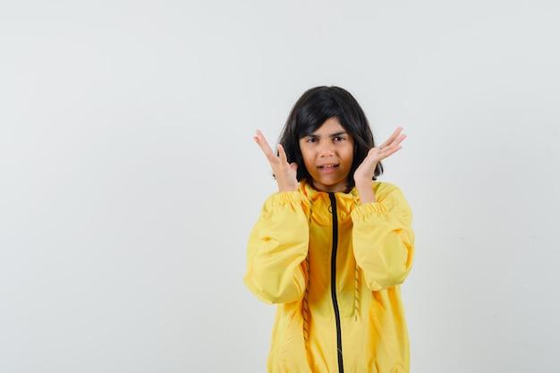 Маленькая девочка в желтой толстовке с капюшоном, взявшись за руки возле головы и выглядя испуганной, вид спереди.