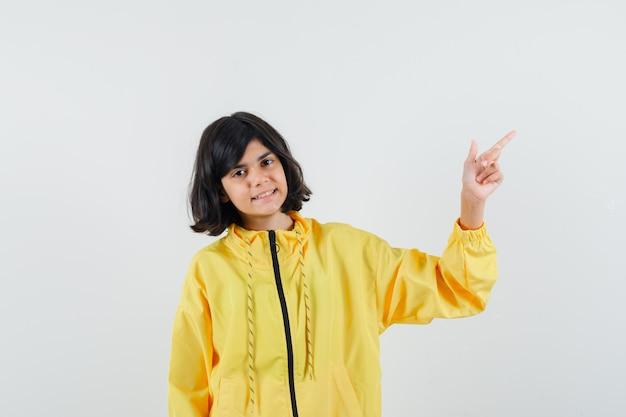 右上隅を指して自信を持って見える黄色いパーカーの少女、正面図。