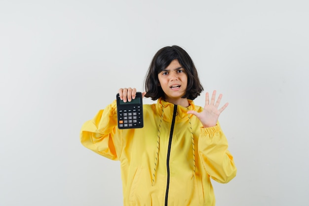 停止ジェスチャーを示し、電卓を保持し、心配そうに見える黄色のパーカーの少女、正面図。