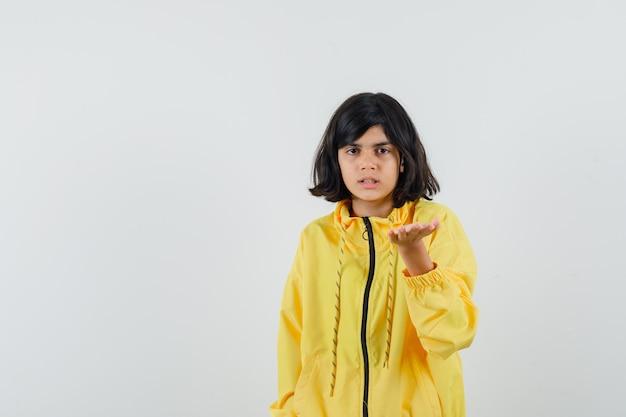 Маленькая девочка в желтой толстовке с капюшоном протягивает руку в вопросительном жесте и недоумевает, вид спереди.