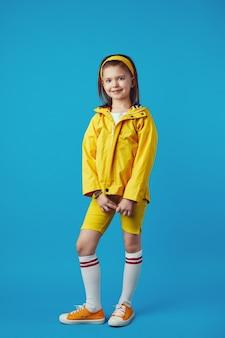 Маленькая девочка в желтом плаще и кроссовках улыбается и держит руки вместе