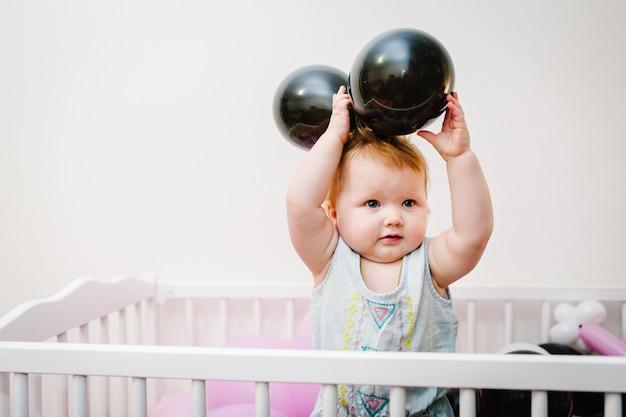 Маленькая девочка-младенец в постели с розовыми, фиолетовыми, пурпурными, цветными надувными шарами на ее день рождения в белой комнате