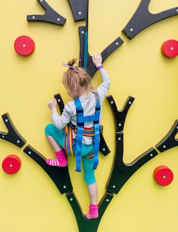 Little girl in insurance trains on climbing wall