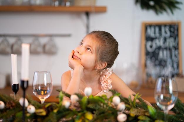 Маленькой девочке скучно сидеть за праздничным столом в рождественскую ночь.