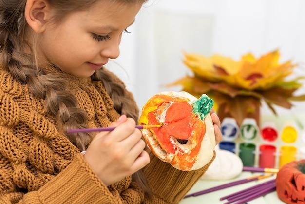 Маленькая девочка раскрашивает тыквы для веселой вечеринки в честь хэллоуина.