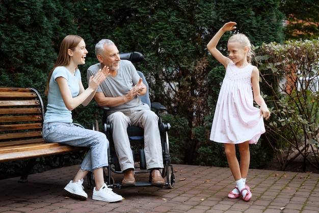 Little girl is dancing, old man and woman are smiling