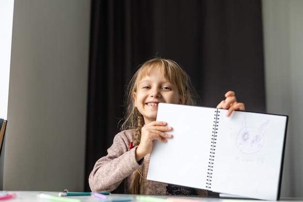 Маленькая девочка делает домашнее задание в начальной школе.