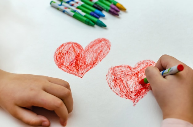 A little girl is drawing a heart with red chalk - high angle image with selective focus. valentine's day concept