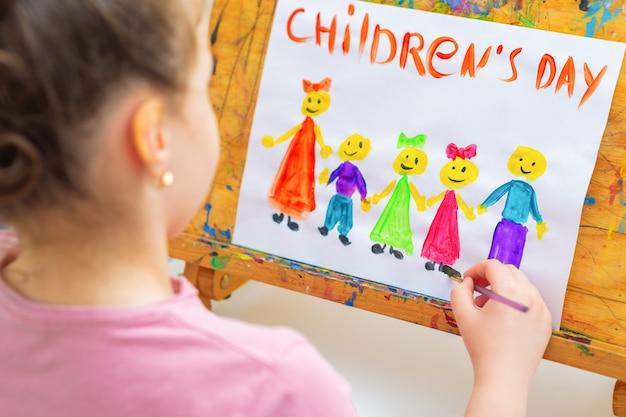 小さな女の子は幸せな休日のために木製のイーゼルで子供の日の言葉で子供たちを描いています