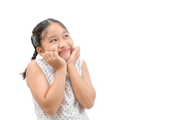 小さな女の子は白い背景、コピースペースで隔離された何かを夢見ているか考えています
