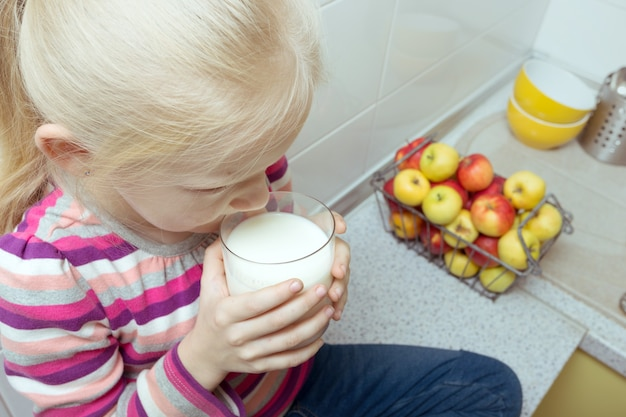 Little girl is drinking milk at the kitchen