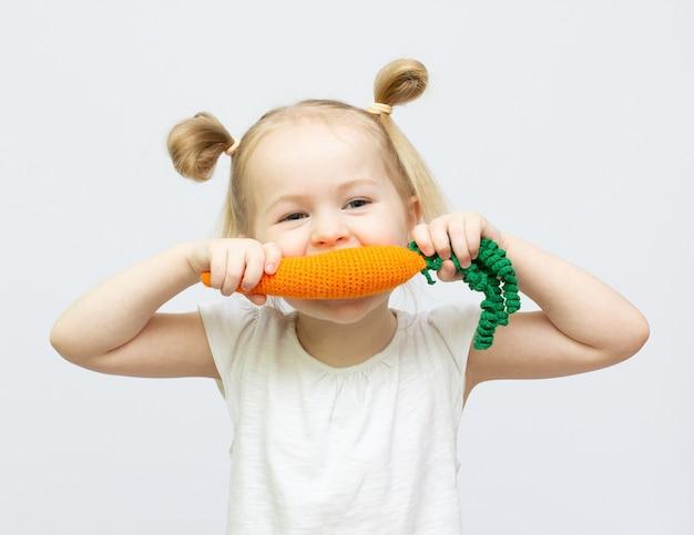 어린 소녀는 흰색 배경에 장난감 knitt 당근 건강 식품을 먹고있다