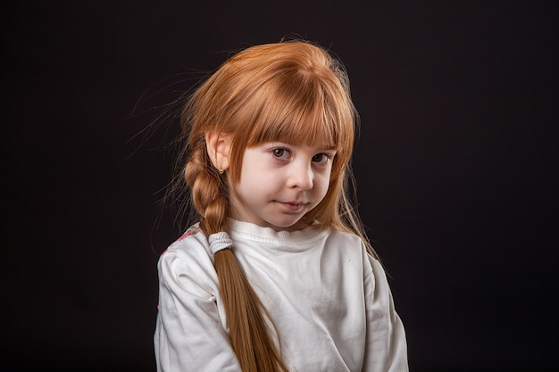 A little girl is embarrassed and costs eyes, a large portrait in a studio on a black background.
