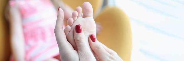 어린 소녀는 평발을 위한 발 마사지를 받습니다.