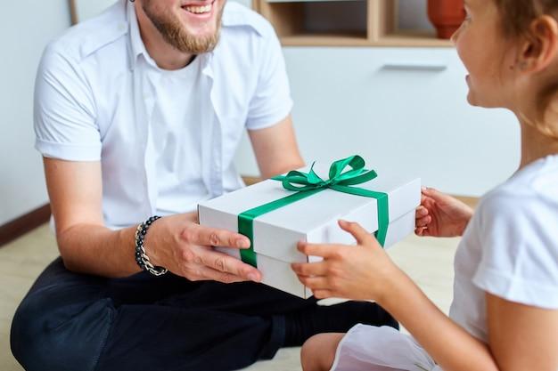 어린 소녀는 아버지의 날에 잘 생긴 아버지에게 선물 상자를주고, 딸이 아빠를 축하하고 집에서 생일 선물을주고 있습니다. 아빠 사랑 해요. 해피 아버지의 날.