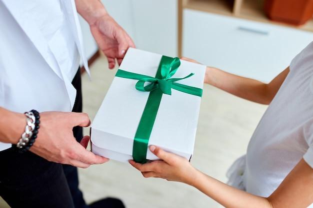 어린 소녀는 잘 생긴 아버지에게 아버지의 날 선물 상자를주고, 알아볼 수없는 딸은 아빠를 축하하고 집에서 생일 선물을주고 있습니다. 아빠 사랑 해요. 해피 아버지의 날.
