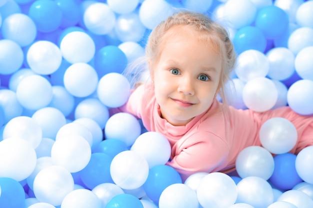 어린 소녀는 공이 있는 수영장에서 즐거운 시간을 보내고 있습니다. 흰색과 파란색 공에 웃는 쾌활한 어린 소녀